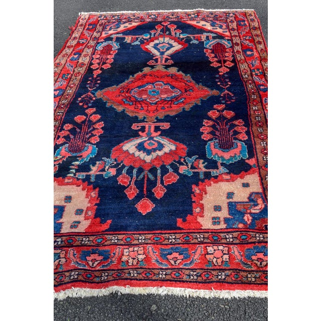 This hand-knotted vintage Persian Rug is a show stopper. The reds, pinks and corals pop off the beautiful navy background...