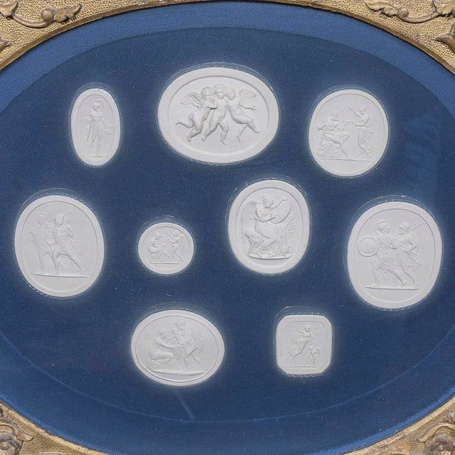 This is a framed wall hanging with 9 various shaped antique plaster neoclassical medallions mounted on a blue velvet....