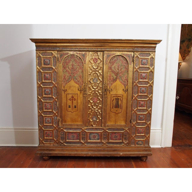 A two door Renaissance style polychrome and gold paint cabinet, the doors arched and each with a simple coat of arms, the...