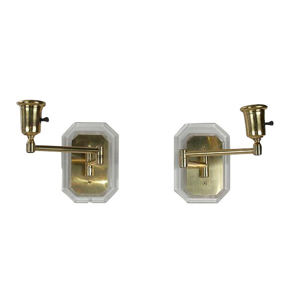A Pair of Lucite and Brass Swing Wall Sconces. Wired for the U.S. and each uses a max. 60 wattage light bulb. Simply...