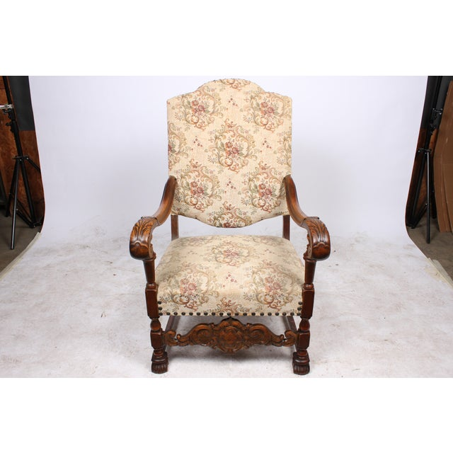 1920s William and Mary revival style armchair featuring carved oak construction and vintage upholstery with brass nail...