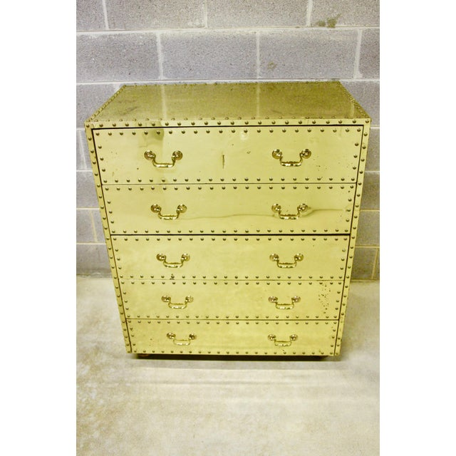 Handsome and iconic 5-drawer dresser by Sarreid. Solid wood construction, clad in brass sheeting with nailhead trim...