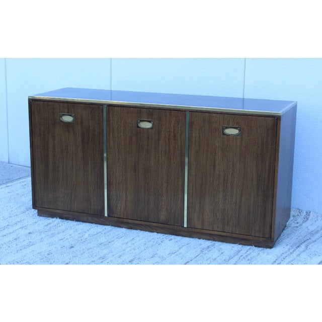 1960s wood and brass credenza by Baker. With two drawers and two adjustable shelves.