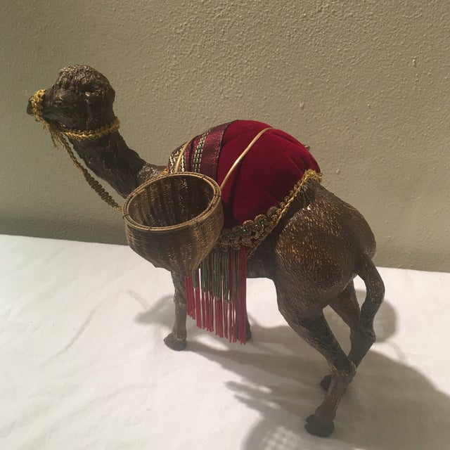 Beautiful vintage camel with velvet and crystal accents. 2 small woven baskets adorn the back saddle