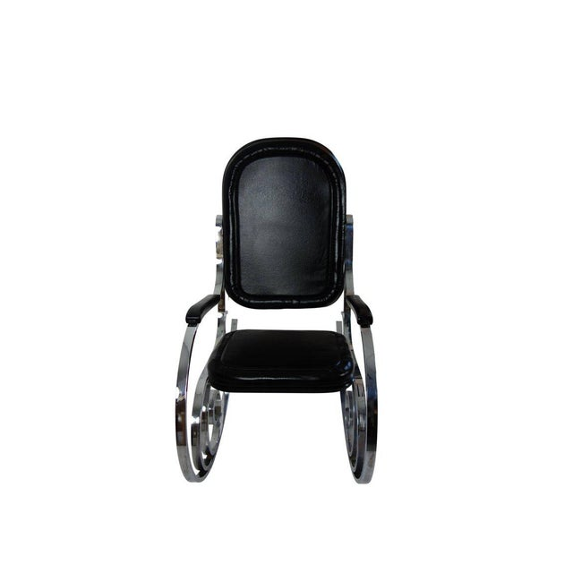 This is a black leather and polished nickel rocking chair by Maison Jansen from France, circa 1970.