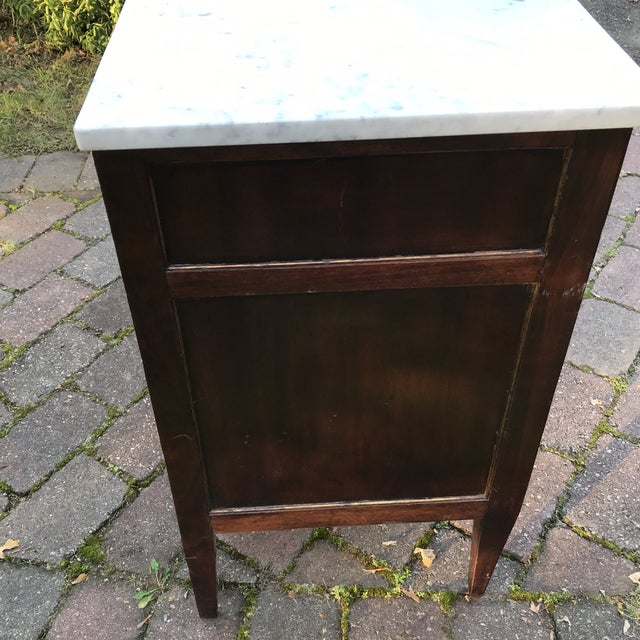 French Empire style Commode with a marble top, brass pulls and three drawers. The legs are square tapered.