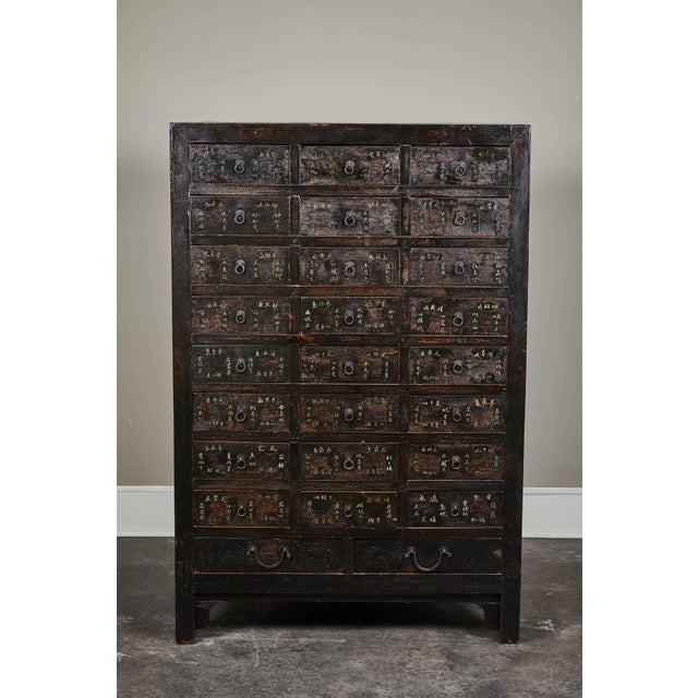 A remarkable 19th century Chinese apothecary cabinet. With 24 drawers and 2 larger lower drawers. Each smaller drawer with...