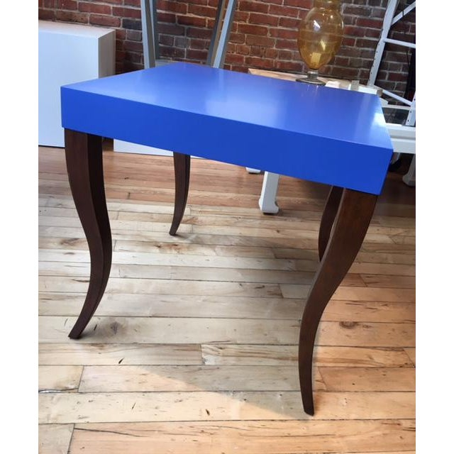 The Gabrielle side table has a lacquered top in Twilight Blue from Benjamin Moore Paints. The stylized cabriole legs are...