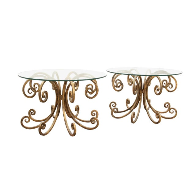 A pair of gold scroll cast iron end tables. Each table has a new pieces of round glass with a smooth edge. The bases are...