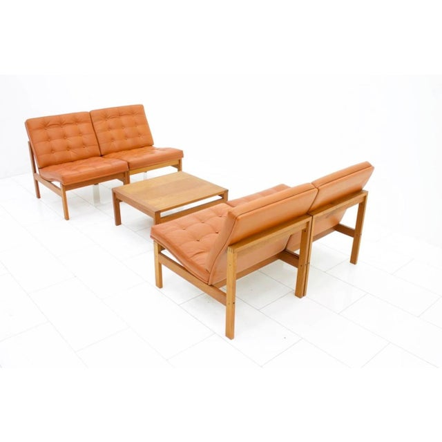 Set of four lounge chairs and a Side Table. Solid teak wood and cognac brown leather by Torben Lind and Ole Gjerlov-...