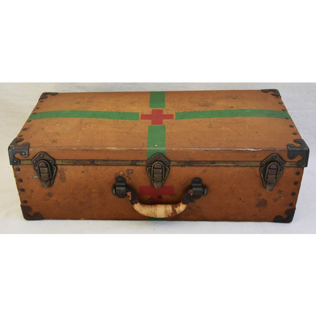 Circa 1940s military medical first aid suitcase with painted green stripes and a red cross on all sides. Has three closing...