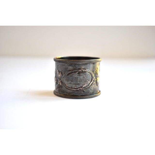 An antique, Victorian, silver plate or silver metal napkin ring, with repousse flowers and a cartouche of branches in an...