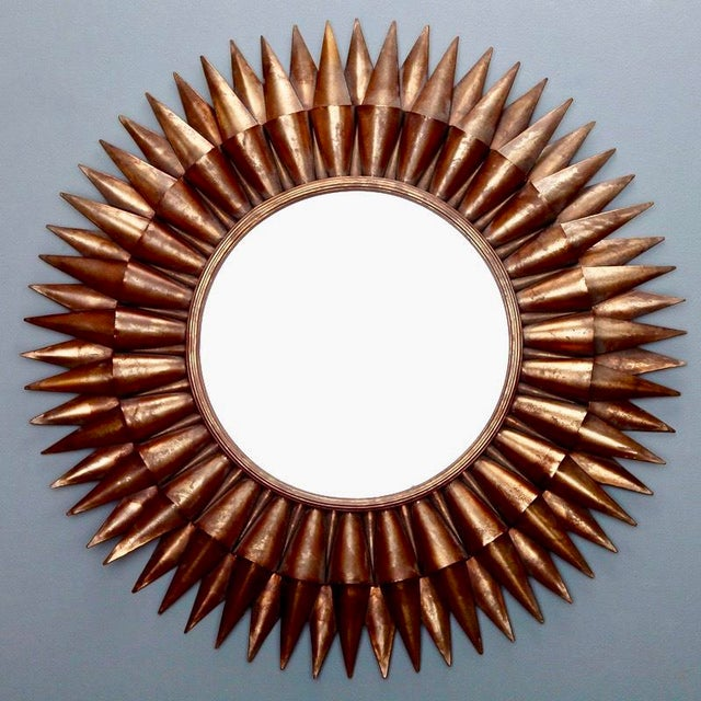 Circa 1970s Spanish sunburst mirror with a two layer frame of gilded metal rays and round center mirror. Actual Mirror...