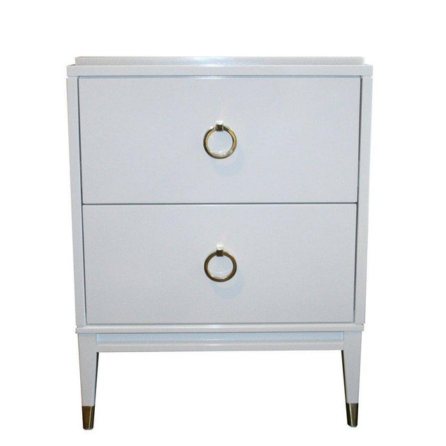 Two-drawer lacquered marble top. Two equal sized drawers are fitted with solid brass ring pulls. Solid apron base with...