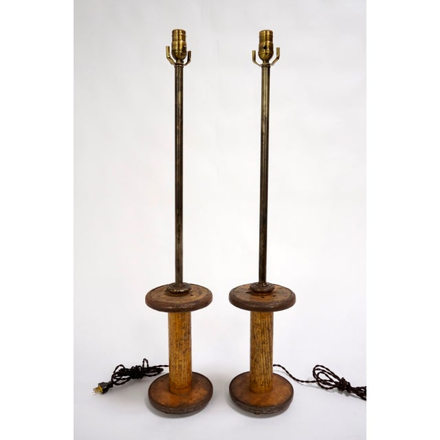 Pair of elegant, weathered, long neck table lamps fashioned from old, industrial wire spools made of wood with metal trim....