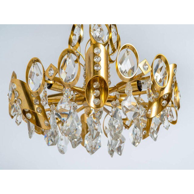 Stunning Mid-Century Modern chandelier with gilded brass frame and cut crystal pendants. Multiple tier design fitted with...