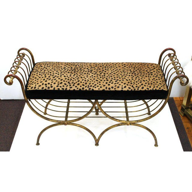Italian mid century modern two seat gilt iron bench with a new seat cushion upholstered in faux leopard leather. The seat...