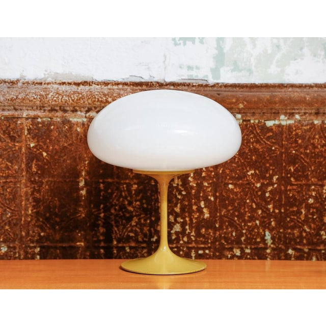 "Modern table light in mustard color with white glass squatted ball shade. Size: 14"" H x 13"" Diameter Year: ca 1960 Status:..."