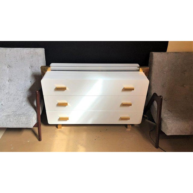 A one of a kind metal lacquered and Lucite important Italian commode or dresser. The gilt metal decorated feet and side...