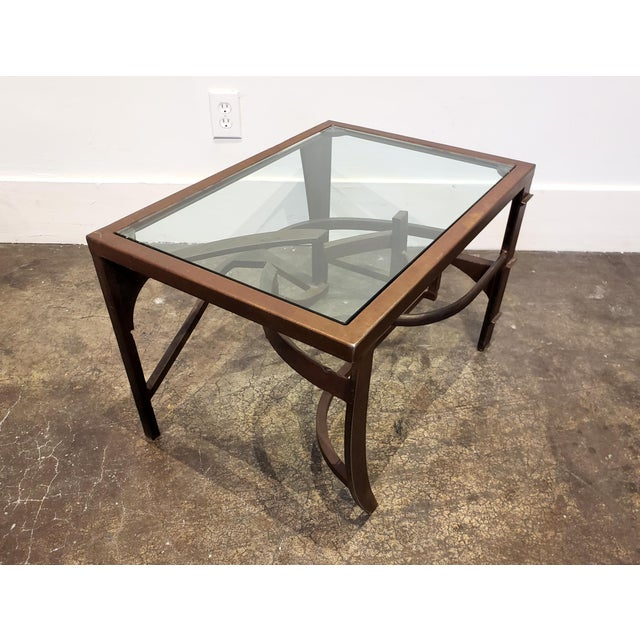 Iron table with dynamic, intertwined sculptural base. Iron has warm patina. Top is finished in glass. Rich in detail and...