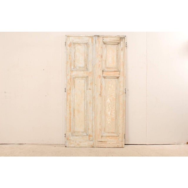 A pair of 19th century French doors. This pair of French doors each feature two recessed panels, with a shorter vertical...