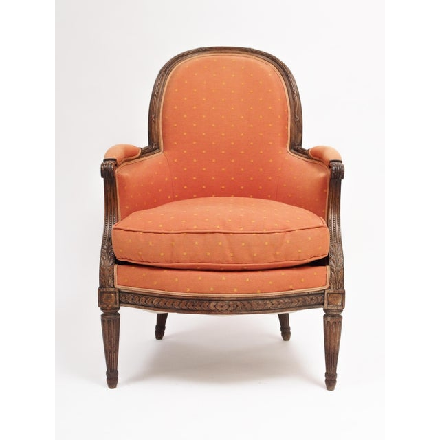 A stately, neoclassical French armchair in the Louis XVI taste, with a reed carved arched back over a commodious seat and...
