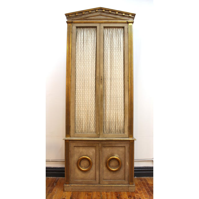 Monumental pair of wood cabinets in Neoclassical Revival style with pedimented tops. The pair has gilt accents and the...