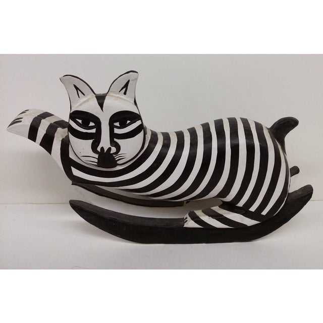 An original hand carved, hand painted folk art cat skiing. This rare and collectible cat has been around the blocks a few...