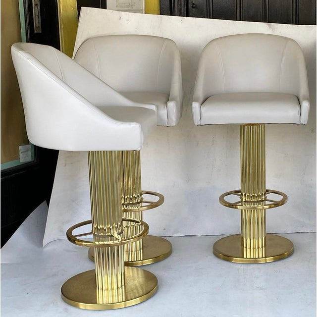 Five designs for leisure barstools… On a neoclassical brass base.. recently reupholstered with high-grade gray vinyl…