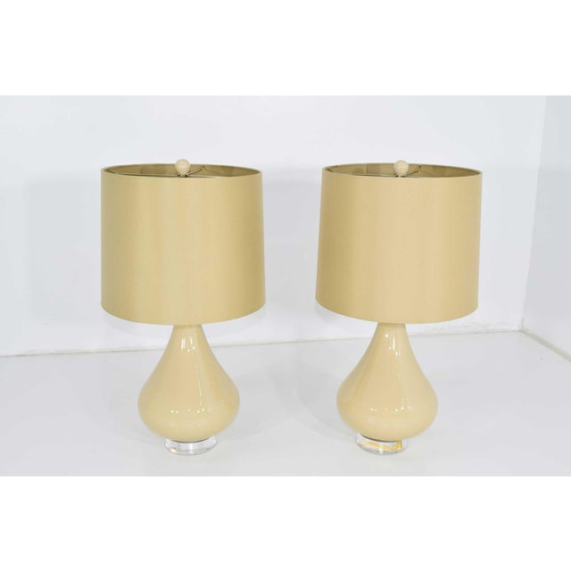 A very nice pair of ceramic lamps with Lucite bases, matching finial and silk shades.