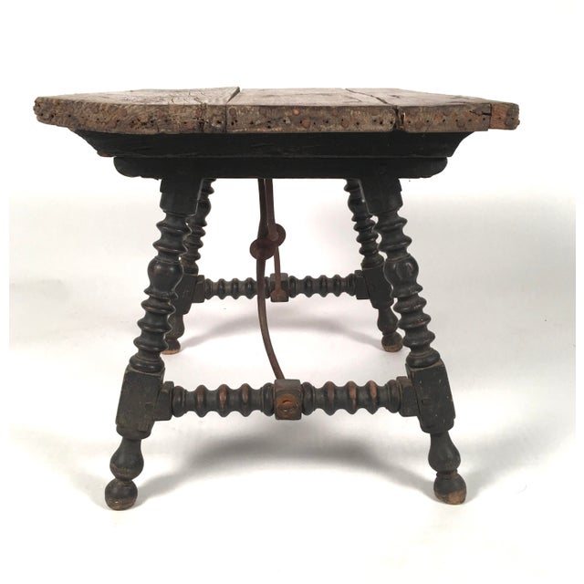 A Spanish Baroque style side table with old, well patinated pine board top supported by four ebonized and turned and...
