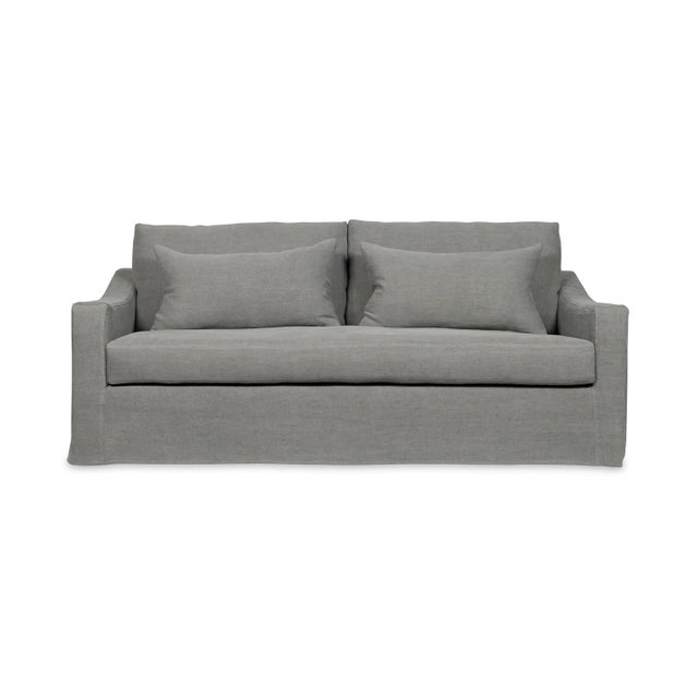 With a wrap around skirt, two included lumbar pillows, and a bench cushion, this slipcovered sofa is simplicity and...