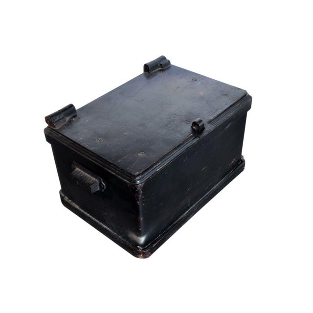 A heavy cast iron strong box that would of been used to hold money or other valuable items and documents. Note, damage...