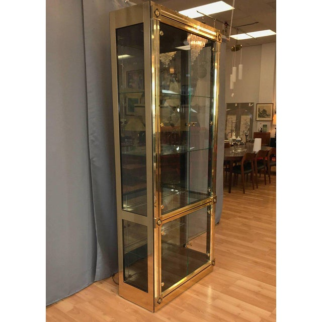 A very uncommon and impressively sized brass vitrine or display cabinet with glass doors and shelves by Mastercraft. Regal...