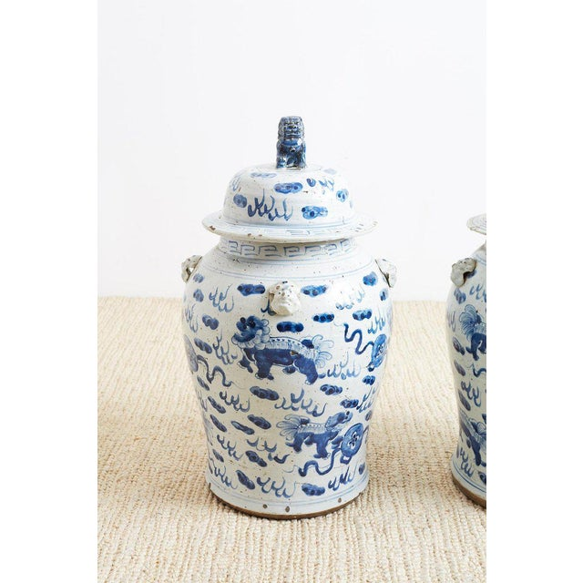 Large pair of Chinese blue and white ginger jars featuring painted foo dogs or lions amid whimsical clouds. Each jar has...