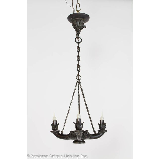 In the style of ancient Roman lamps with a central base and three lighted arms. Faces with classical braided hair. Made in...