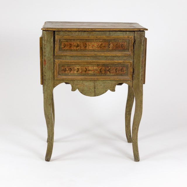 A fanciful painted Italian Commode, circa 1720, painted a soft earthy green with ochre bordered panels of painted foliate...