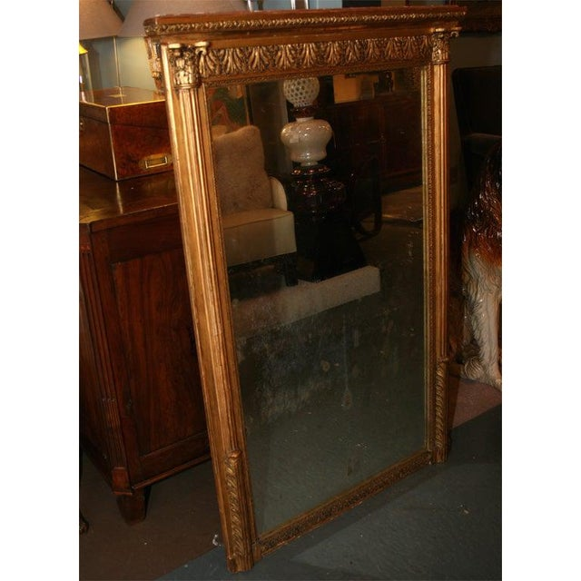 An elegant Louis XVI style giltwood mirror, carved with architectural motifs including side reeded columns and molded top,...