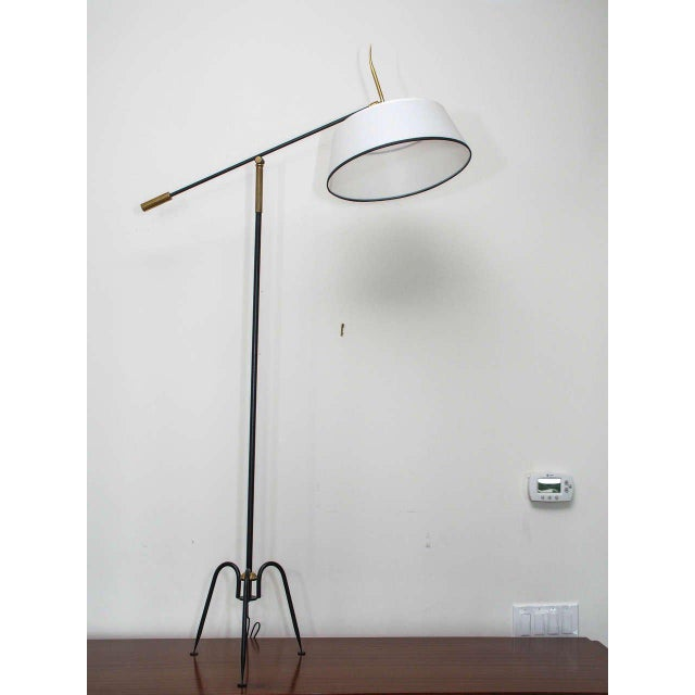 Stylish floor lamp in iron and bronze with beautifully detailed workmanship throughout; tripod base; paper shade with...