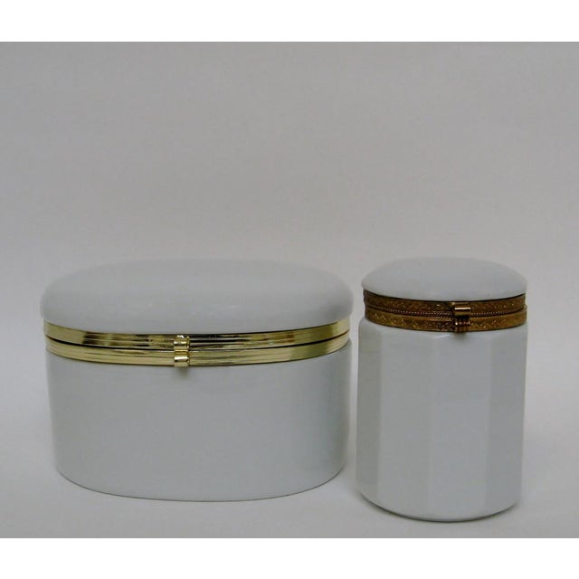 This is a pair of coordinating white gloss glazed porcelain vanity canisters with gold metal hinges. There are two sizes...