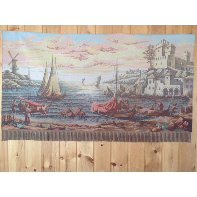 Woven on a loom, this vintage wall tapestry depicts a Dutch port scene complete with fishing boats, a castle, and a wind-...