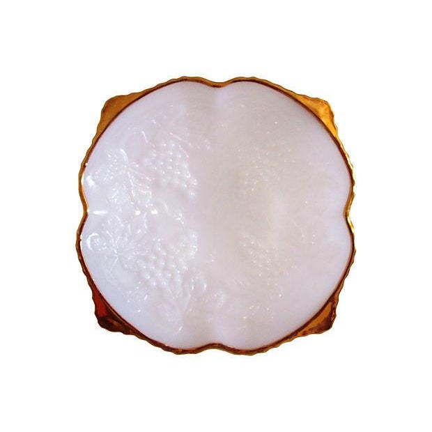 Vintage white square-shaped milk glass bowl featuring heavy gold-embellished rim and raised grape-cluster motif on face of...