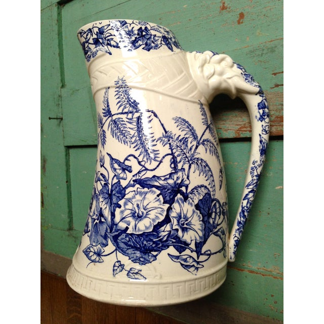 Very unusual antique large curved blue transfer ware pitcher. This unique antique pitcher boasts a rare embossed elephant...