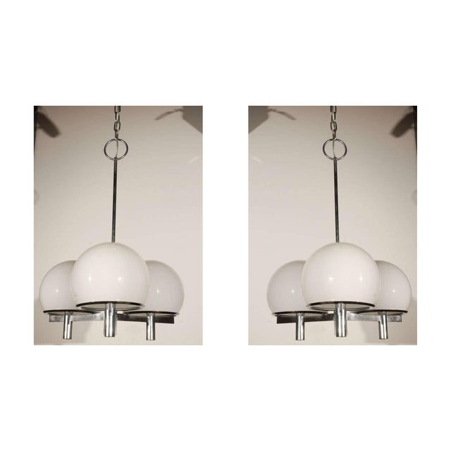 Three white globe Lightolier ceiling fixture. Two ceiling fixtures available. Three pairs of matching sconces available....