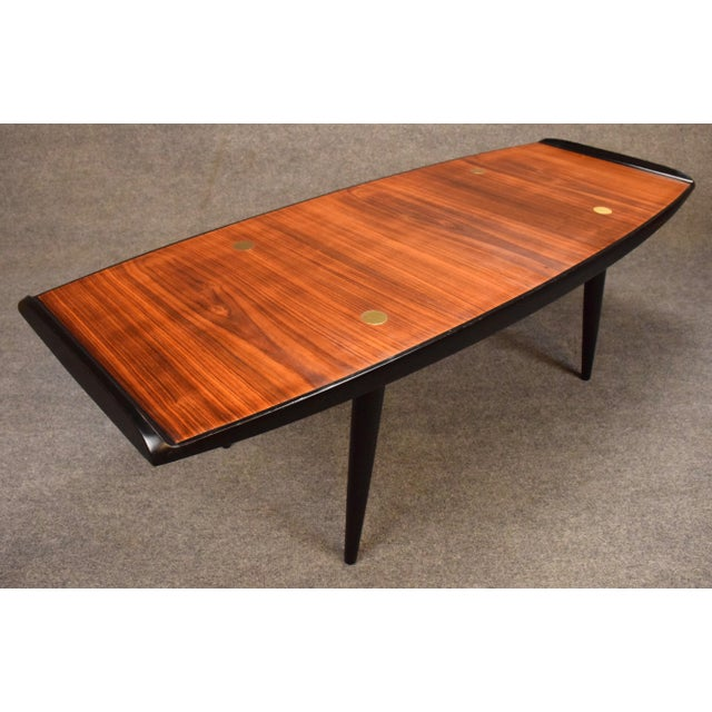 Here is a very unique 1960's Scandinavian modern coffee table with a rosewood top, a contrasting black lacquered frame and...