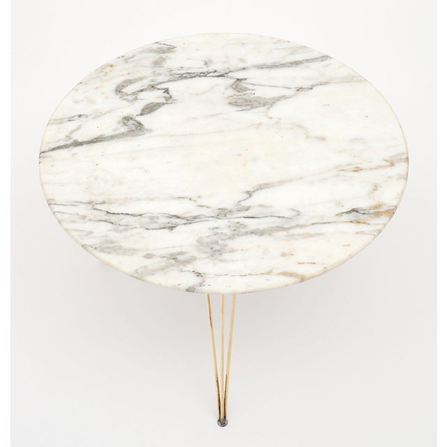Vintage Italian mid-century marble table with a beautiful Carrara marble top and gilt brass tripod base feet. A superb...