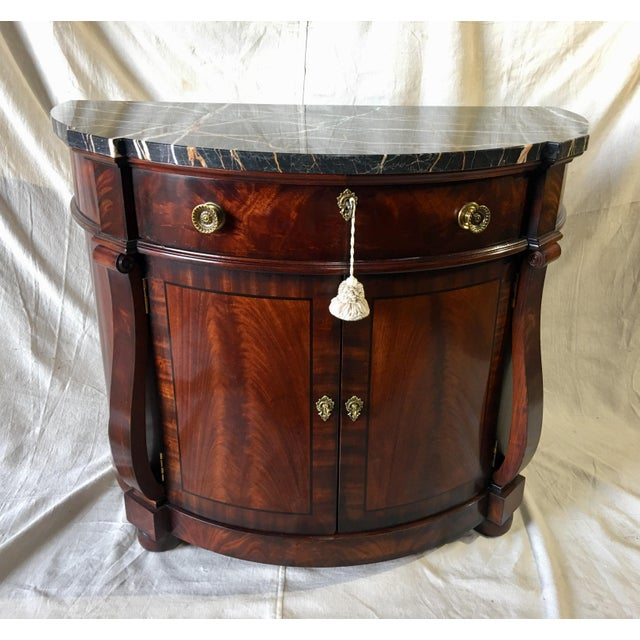 A Henredon Natchez mahogany demilune side table. The stately piece from Henredon's Natchez collection features old world...