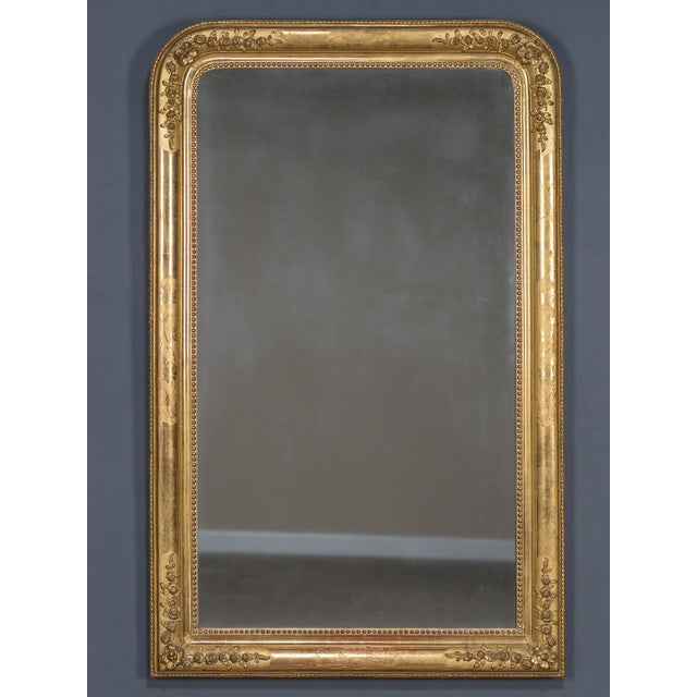 The elegant decoration on this antique French mirror circa 1880 is placed in a symmetrical manner with both raised and...
