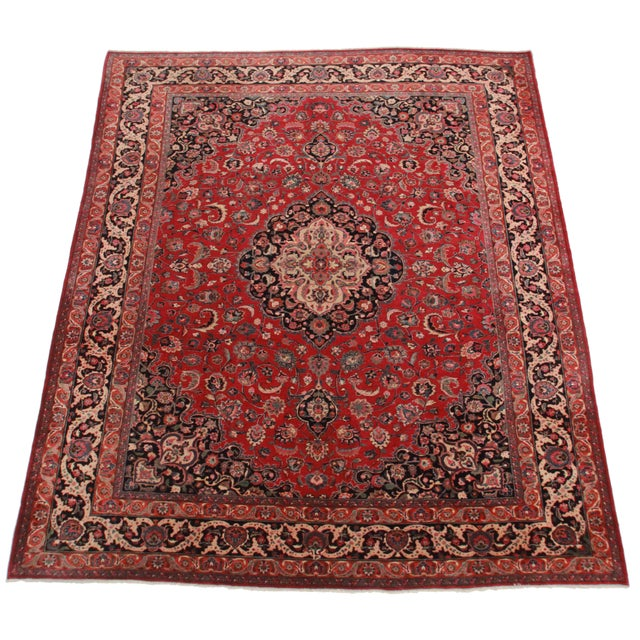 Crafted of hand-knotted wool, this Persian Mashad rug features a floral design.