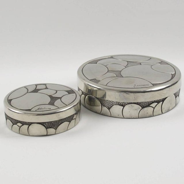 Elegant set of two French Art Deco polished pewter boxes by Rene Delavan. Round lidded shape with carved and embossed...